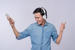 Handsome young man wearing headphones and holding mobile phone w Royalty Free Stock Image