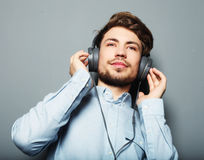 Handsome young man wearing headphones and listening to music. Stock Photos