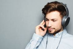 Handsome young man wearing headphones and listening to music. stock photo
