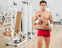 Handsome young man wearing red shorts. Lifting weights and looking on you Stock Photography