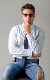 Handsome young man wearing shirt, necktie and ripped jeans Royalty Free Stock Images