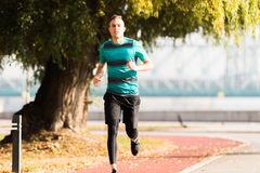 Handsome young man wearing sportswear and running at quay during Stock Photo