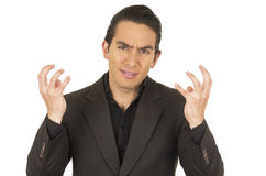 Handsome young man wearing a suit gesturing anger. Handsome elegant young latin man wearing a suit gesturing anger isolated on white Stock Images