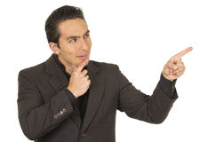 Handsome young man wearing a suit posing pointing Stock Photos