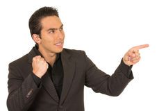 Handsome young man wearing a suit posing pointing Royalty Free Stock Images