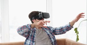 Man wearing vr headset and gesturing on sofa stock video footage