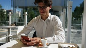 Young man typing on cell phone outdoor. Handsome young man wearing white t-shirt and glasses sitting at outdoor cafe and typing on cell phone, looking down at stock footage