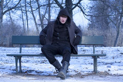 Handsome young man wearing winter jacket. Handsome young man wearing winter jacket sitting on a bench in blue and cold winter scenery Royalty Free Stock Image