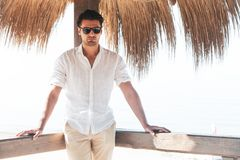 Handsome young man with white shirt and sunglasses relaxed leaning on a wooden bar royalty free stock images