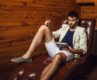 Handsome young man in white suit relaxing on luxury sofa with diary. Photo royalty free stock images
