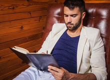 Handsome young man in white suit relaxing on luxury sofa with diary. Photo stock photography