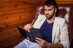 Handsome young man in white suit relaxing on luxury sofa with diary. Photo royalty free stock photography