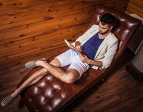 Handsome young man in white suit relaxing on luxury sofa with diary. Photo royalty free stock photo