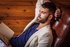 Handsome young man in white suit relaxing on luxury sofa with diary. Royalty Free Stock Photos