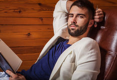 Handsome young man in white suit relaxing on luxury sofa with diary. Royalty Free Stock Photo