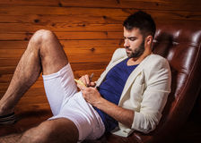 Handsome young man in white suit relaxing on luxury sofa with diary. Photo stock photo