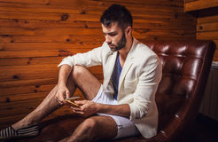 Handsome young man in white suit relaxing on luxury sofa with diary. Photo stock image