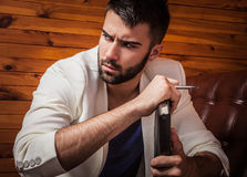 Handsome young man in white suit relaxing on luxury sofa with diary. Photo stock photos