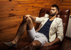 Handsome young man in white suit relaxing on luxury sofa. Photo stock image