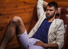 Handsome young man in white suit relaxing on luxury sofa. Photo stock photos