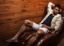 Handsome young man in white suit relaxing on luxury sofa. Photo stock photography