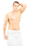 Handsome young man in white towel posing after shower Stock Images