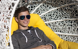 Handsome young man in a wicker chair close-up stock images