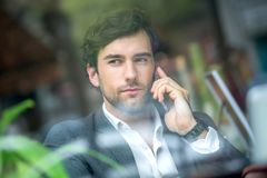 A handsome young man in the window stock photography