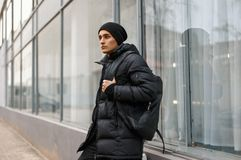 Handsome young man in winter jacket with a backpack posing Stock Photo