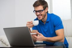 Handsome young man working on computer laptop at home. Royalty Free Stock Photo