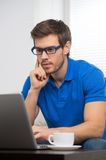 Handsome young man working on computer laptop at home. Stock Photo