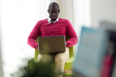 Handsome young man working with his laptop at home. Stock Photo