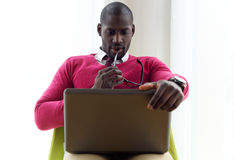 Handsome young man working with his laptop at home. Portrait of handsome young man working with his laptop at home Royalty Free Stock Photos