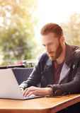 Handsome young man working on laptop. At cafe Royalty Free Stock Photo
