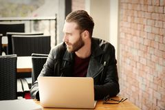 Handsome young man working on laptop at. Cafe Royalty Free Stock Photography