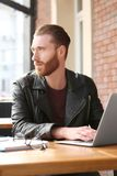 Handsome young man working on laptop at. Cafe Stock Image