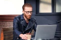 Handsome young man working on laptop. Outdoors Stock Images