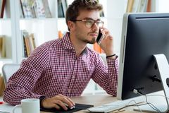Handsome young man working with laptop and mobile phone in the office. Stock Photo