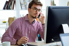 Handsome young man working with laptop and mobile phone in the office. Stock Image