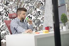 Handsome young man working with laptop in office stock photos