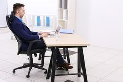 Handsome young man working with laptop. Incorrect posture concept. Handsome young man working with laptop in office. Incorrect posture concept Royalty Free Stock Images