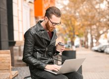 Handsome young man working on laptop. Outdoors Royalty Free Stock Image