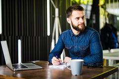 Handsome young man working on laptop and smiling while enjoying coffee in cafe Stock Photo