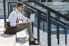 Handsome young man working with laptop on stairs. On city street Stock Photography