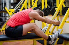 Handsome young man working out on gym equipment Stock Photos