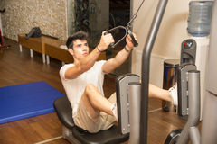 Handsome young man working out on gym equipment Royalty Free Stock Photography