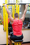 Handsome young man working out on gym equipment Royalty Free Stock Images