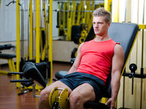 Handsome young man working out on gym equipment. Attractive and fit young man in gym working out legs and exercising on equipment Stock Photo