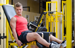 Handsome young man working out on gym equipment. Handsome young man working out, exercising legs on gym equipment Stock Photography