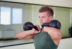 Handsome young man working out in gym with kettlebells Stock Images